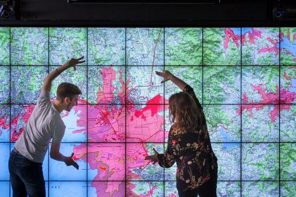 Eugénie Brasier et Raphaël James, stagiaires Inria / LRI au sein de l'équipe-projet Ilda. Vue globale du bassin caribéen dans l'encadré, avec la zone de propagation du tsunami. Mapmuxing, projet ANR avec l'IGN. Il y a eu un séisme vers le Venezuela, qui a provoqué un tsunami qui arrive sur la Martinique: on est en gestion de crise, on voit les zones à évacuer en rouge, les points sont les bateaux (en noir = ok, en orange = trop près des côtes donc à évacuer); la très haute définition permet de zoomer pour voir des informations sur le bateau comme le nombre de passagers et membres d'équipage. En savoir plus sur MapmuxingLa plateforme Wilderest un mur d'images tactile de 12 m2, 70 millions de pixels. Comme il faut parfois s'éloigner du mur pour mieux voir, on peut interagir avec le mur via une tablette. Il y a un système de capture de mouvement également.Projet Inria / CNRS / Université Paris Sud